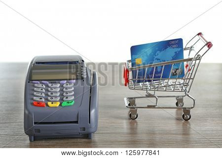 Payment terminal with supermarket trolley and credit card on wooden table