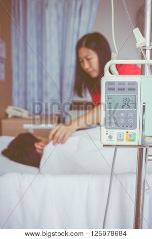 Illness asian child lying on sickbed with infusion pump intravenous IV drip. Mother take care her son. Shallow depth of field IV machine in focus. Health care and medical concept. Vintage style.