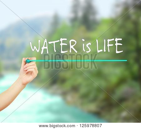 Save water concept. Water is Life text and hand with marker on blurred natural background