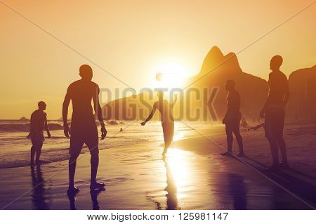 Silhouette of unidentified, unrecognizable locals playing ball game at sunset in Ipanema beach, Rio de Janeiro, Brazil.