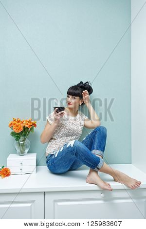 Young attractive woman drinking red wine at home. Relax after work. Girl barefoot.