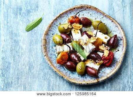 Marinated habanero peppers, olives and feta cheese on a ceramic plate (mediterranean-style antipasto)