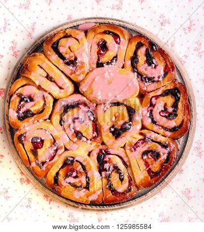 Fruity iced swirl buns on wooden board
