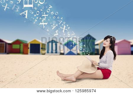 Portrait of happy female model sitting on the beach while using a digital tablet with the background of the beach hut