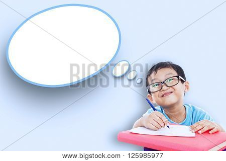 Image of male elementary school student studying and writes on the paper with empty speech bubble