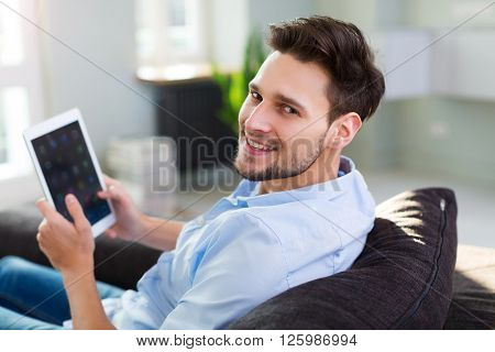 Man sitting on couch with digital tablet