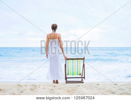 Beautiful woman in white dress standing nearby deckchair on the beach and enjoying the scene.