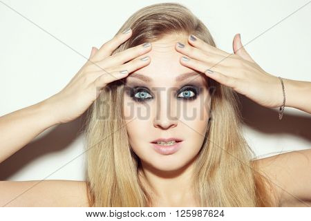 Portrait of young attractive blond woman touching her wrinkled forehead with worried expression