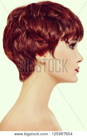 Vintage style profile portrait of young beautiful redhead woman with short haircut