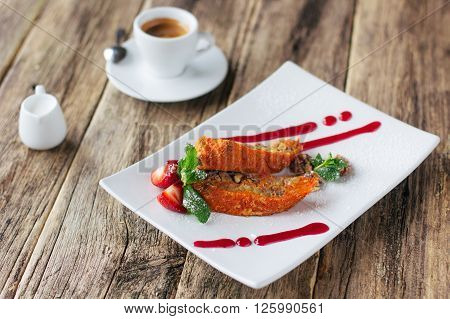 Vegetarian dessert. Carrot apple  sweet roll  with a strawberry sauce and a cup of espresso coffee served on wooden background. Lenten vegetarian desert from fruits.
