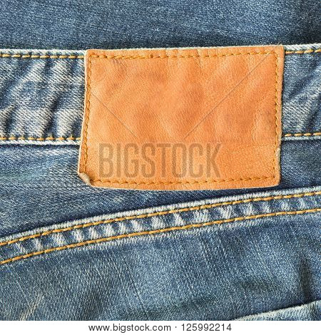 brown leather tag on black jeans, clothing industry