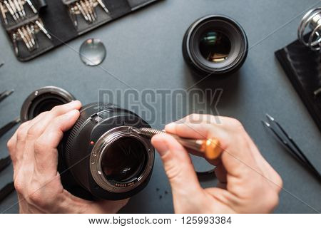 Photo camera lens repair set. Technician engineer check optics alignment and maintenance support of broken photographic 85 1.2 photo camera lens part. Pov to workshop and engineer's hands.