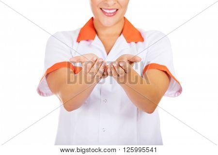 Smiling female doctor or nurse shows something