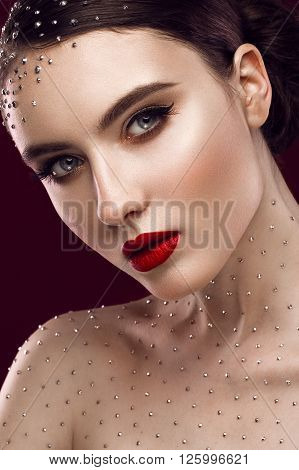 Portrait of a beautiful girl with a bright make-up red lips curls and crystals on the body. The beauty of the face. Photos shot in the studio.