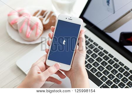 Alushta Russia - October 29 2015: Woman holding iPhone6S Rose Gold with social networking service Tumblr on the screen. iPhone 6S Rose Gold was created and developed by the Apple inc.
