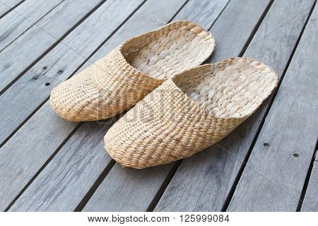 Vintage slippers handmade with bamboo on wood floor.