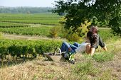 image of naturel  - Couple sat on the grass in front of vineyards - JPG