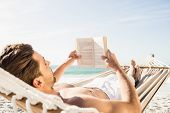 Man reading book in hammock on the beach poster