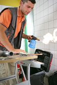 Man warming a pipe in metal with a blowtorch poster