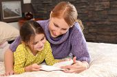 foto of girl reading book  - Portrait of a young woman and a little girl stretched out on a bed reading a book - JPG