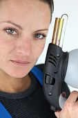 Portrait of a young woman holding a blowtorch poster