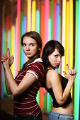 Two Beautiful Young Women Posing Over Colorful Background