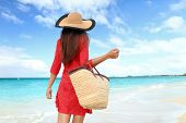 Woman tourist walking on tropical summer vacation wearing sun hat, red dress and beach bag relaxing  poster