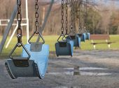 pic of swingset  - empty swingset in a park with focus on first swing - JPG
