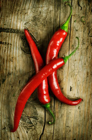 picture of red hot chilli peppers  - Red Hot Chili Peppers over wooden background - JPG