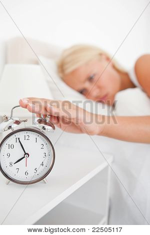 Portrait Of An Unhappy Woman Switching Off Her Alarmclock