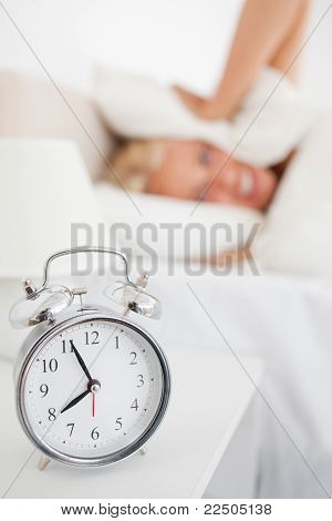 Portrait Of A Woman Hidding Her Head In A Pillow While The Alarm