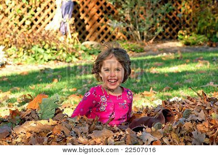 Young girl jumps into a pile of autumn leaves