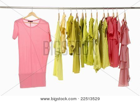 Shirts with brightly colored collars hanging on wooden clothes hangers