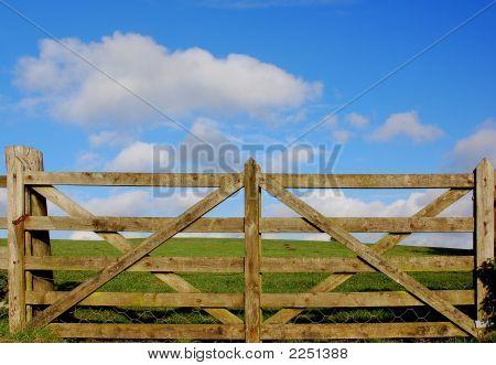 Holzzaun mit Grünland und Himmel