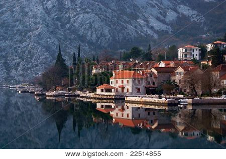 Waterscape With Old Town Against Mountain With Perfect  Mirror Image