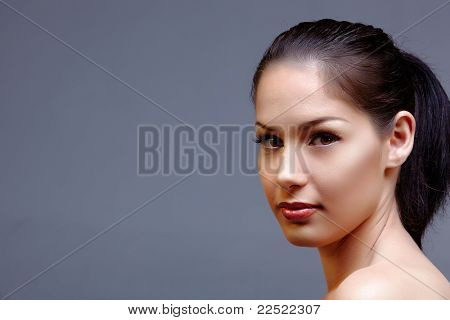 beautiful woman with long black hair in ponytail wearing classic natural make-up and beautiful skin texture over dark studio background with text space