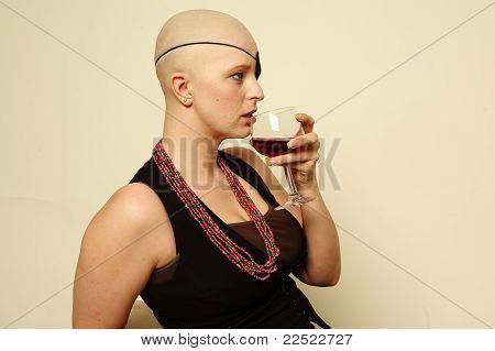 Bald girl drinking wine