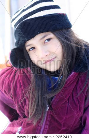 Spunky Little Girl In Winter Clothing Posing Outdoors