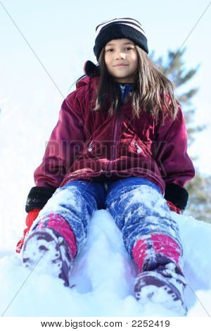Young Girl In Winter Attire Playing On Top Of Snow Hill