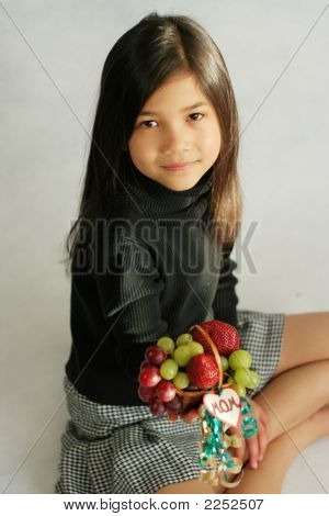 Eight Years Old Girl Holding Up Small Basket Of Fruit