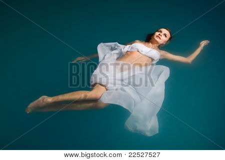 sexy woman floating on swimming pool in white dress
