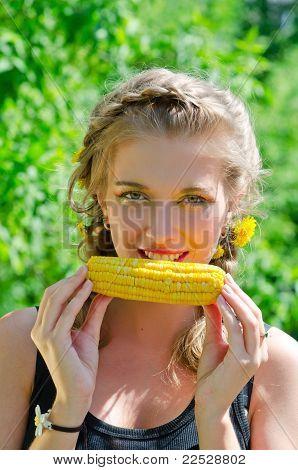 mujer comiendo mazorca de maíz