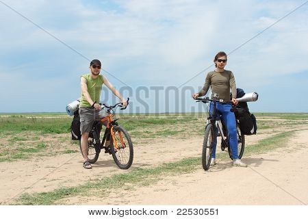 Two Bicycle Tourists Standing On Road, Blue Sky And Horizon