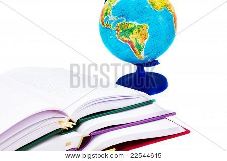 pile of open books and globe