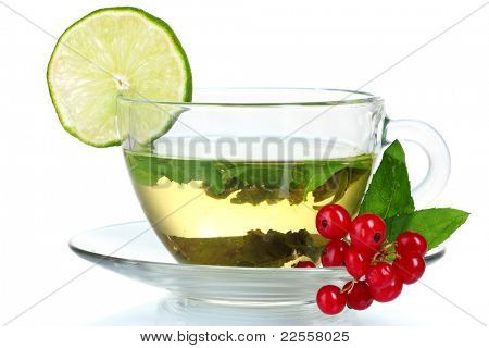 green tea in transparent cup with lime and berry isolated on white