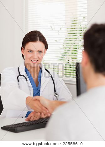 A female doctor is shaking hands with a patient and looking to the camera