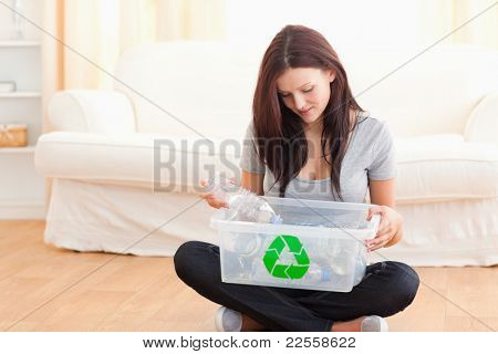 Cute woman putting bottles in a recycling box in her home