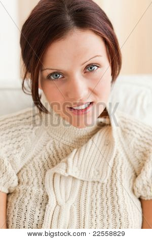 Close up of a smiling cute woman in a living room