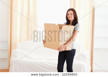 A woman is carrying a cardboard
