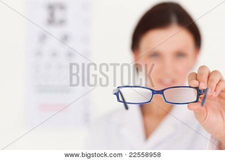 A blurred female optician showing glasses